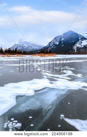 A cold, foggy Winter morning at frozen Vermilion Lakes in Banff National Park with ice beneath the surface and Mount Rundle in the background.
