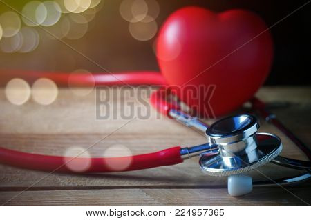 steth and red heart shape with glass of water on wood table, concept of healthy care