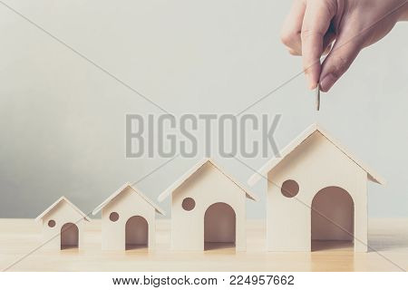 Property investment and house mortgage financial concept, Hand putting money coin in wooden houses arranged different size in row