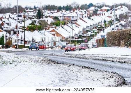 Cloudy Day Winter View of Typical English road under snow in Northampton town.