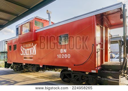 Nebraska, USA - Aug 8, 2017: Restored vintage red train carriage on public display at the Lincoln Haymarket area. Open to mainly pedestrian traffic, this area has a strong railroading heritage.