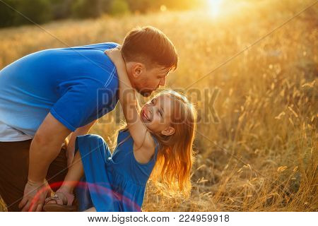 Family values. The daughter is hanging on the father's neck. They are walking in the field at sunset. Joy of paternity. Solar glare.