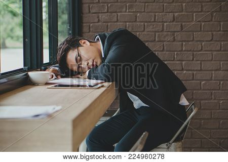 Young business man sleeping on desk  in office. Overworked and tired.