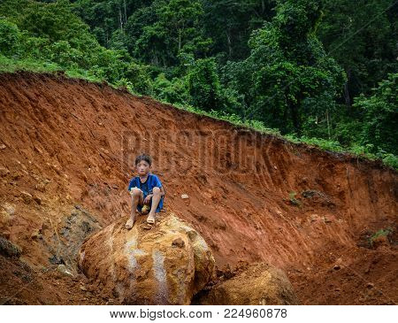 A Boy Sitting On Rock