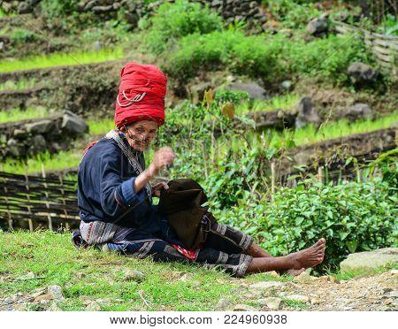 Sa Pa, Vietnam - May 31, 2016. An Old Woman Sewing On Rural Road In Sa Pa, Vietnam. Sa Pa Is A Mount