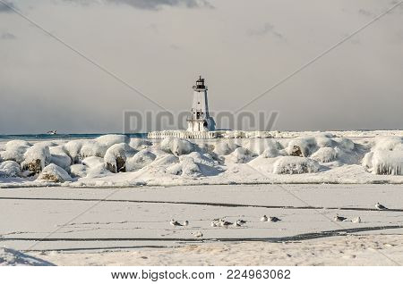 Focus is on North Breakwater Light with ice and rocks.