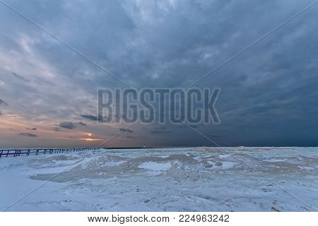 Frozen foreground leads to water and a sunset on Lake Michigan at Ludington's North Breakwater Light at Stearns Park