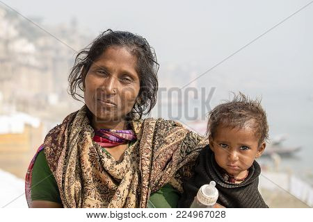 VARANASI, INDIA - JANUARY 26, 2017 : Portrait mother and children on the street at the ghats of Varanasi, Uttar Pradesh, India