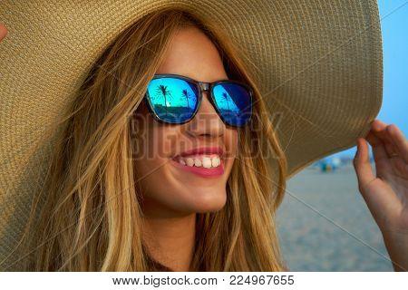 Blond teen girl sunglasses and pamela sun hat at palm tree sunset
