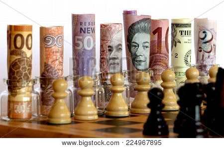 Chess pieces and cash on a chess board.