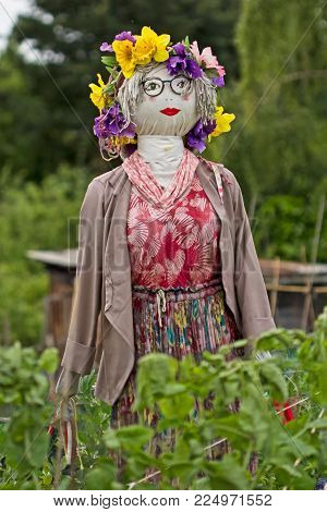 Attractive scarecrow dressed in pink coat and red dress with flowers on her head