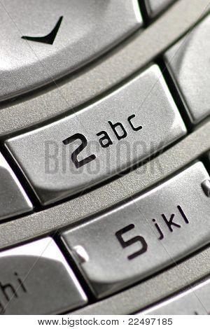 Close-up of phone keypad, emphasizing '2abc' key.