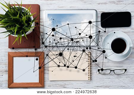 Top view of modern workplace with office stuff and social network connection above as symbol of still office life. Mixed media.