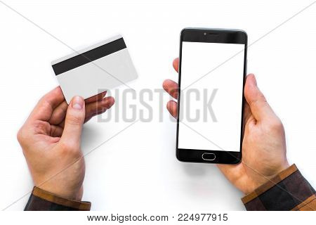 A black smartphone mock up and a credit card in the hands of a man on a rural white background, concepts of Internet commerce and the use of online banking to pay for services and goods