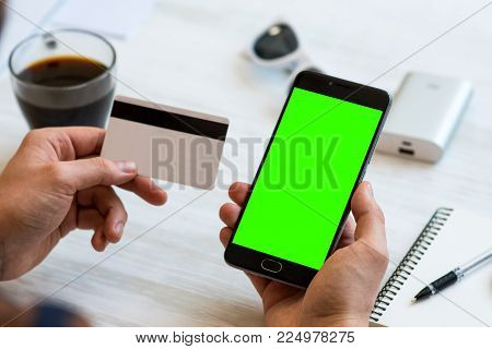 smartphone with green screen for chroma key compositing and a credit card in the hands of a man on white background, of Internet commerce online banking to pay for services and goods in Internet