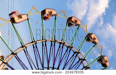 The cars are mostly upside down and empty on this round of a ferris wheel type carnival ride