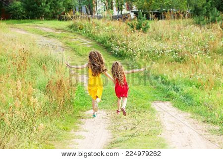 Two little sisters running and playing on the road in countryside on a warm summer sunset. Cute little girls