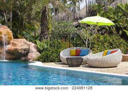 Beautiful tropical beach with swimming pool, coconuts palm trees, rattan daybeds and umbrella in a tropical garden near sea, Thailand
