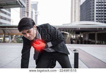 Business man is clutching his chest, acute pain possible heart attack with copy space.