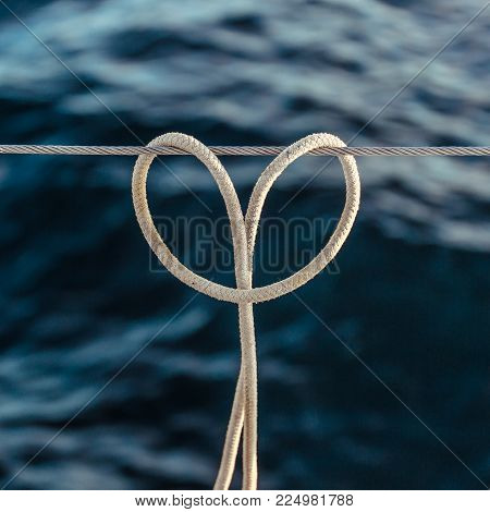 The rope knot (hitch knot) on a steel cable, heart shaped on background of ocean.