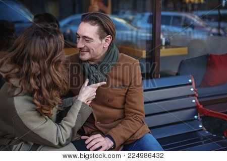 Affectionate young woman is adjusting scarf of man with care. He is looking at lady with fondness and smiling. Romantic date outdoor concept. Copy space poster