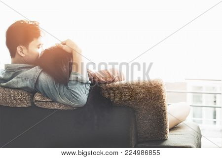 Lifestyle Couple in love and relaxing on a sofa at home and looking outside through the window of the living room, sunny day.  Valentine and Lifestyle Concept