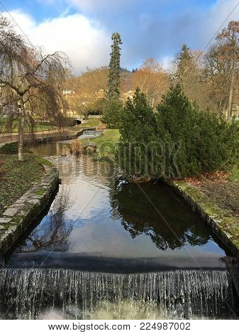 Narrow River In The Park, Sunny Winter Day, Different Types Of Trees, Coniferous Green And Deciduous