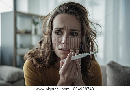 Frightened girl is shocked about her pregnant state. Focus on pregnancy test stick with two strips on it. Portrait