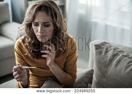Portrait of anxious girl looking at pregnancy test with despair. Unwanted pregnancy concept