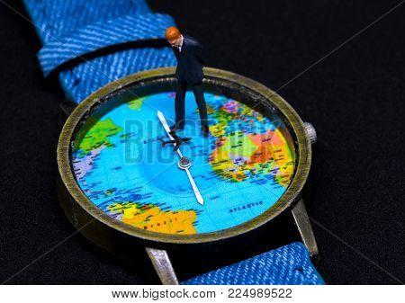 Businessman figurine on watch. World map clock. Worldwide business concept. Businessman macro photo. Global corporation strategic planning decision. Global business. Worldwide business travel jet lag