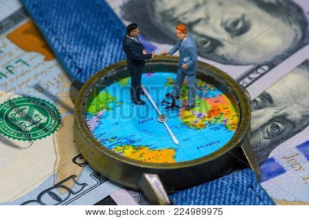 Two businessman figurines on time and money background. Worldwide business concept. International business agreement. Global corporation strategic partnership. Global business profit. Global market
