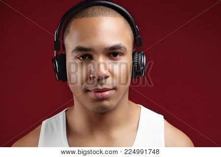 Studio shot of smiling confident young African American clean shaven man enjoying new album of his favourite artist via stylish headphones, using online music application on some electronic device