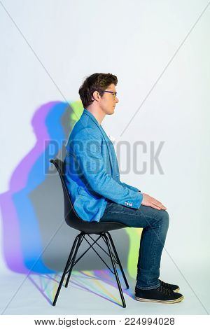 Full length side view profile serious businessman sitting on chair. He putting hands on legs. Demureness concept