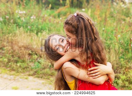 Two Cute little girls embracing and laughing at the countryside. Happy kids outdoors