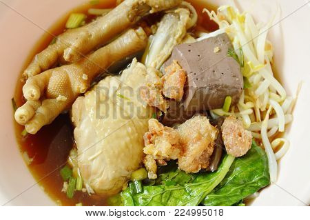 braised chicken leg and feet with bean sprout in herb brown soup on bowl