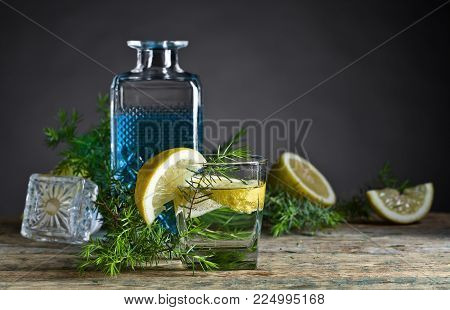 Cocktail with blue gin , tonic and lemon on a old wooden table .