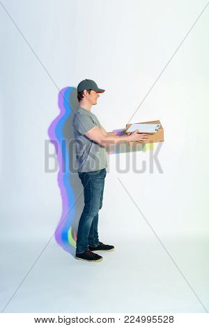 Full length side view outgoing postman keeping package with documents. Shipment concept