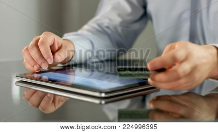 Male hands making online noncash payment on tablet, inserting bank card details HD