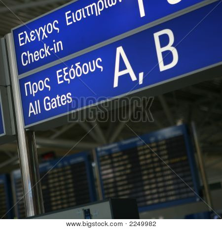 A sign to the boarding gates in English and Greek at Eleftherios Venizelos International Airport Athens. The flight departures information board is out of focus in the background poster