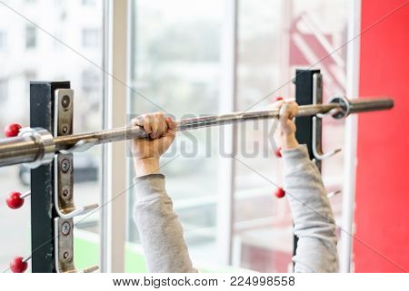 Arms of man working out in the gym, beginner athlete doing bench press exercise