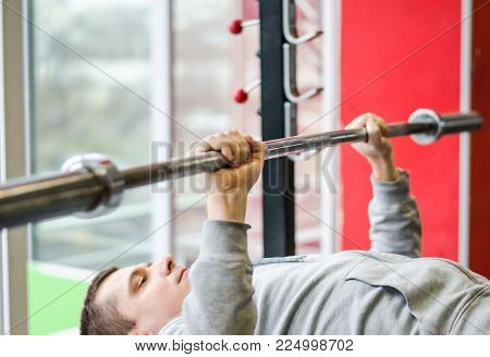 Young male patient doing bench press exercise at medical rehabilitation center