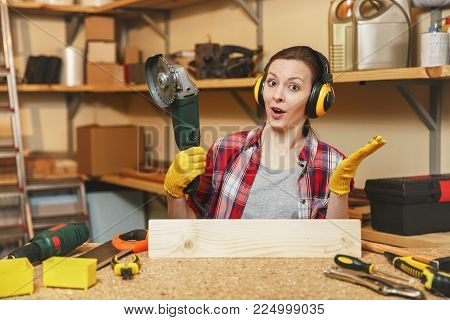 Young brown-hair woman in plaid shirt, gray T-shirt, noise insulated headphones, yellow gloves working in carpentry workshop at wooden table place with different tools, sawing wood with power saw