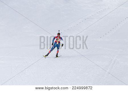 Biathlon racing, biathlete skiing with rifle on his back