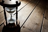 Hourglass time passing concept for business deadline, urgency and running out of time poster