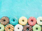 Top view of assorted donuts on blue concrete background with copy space. Colorful donuts background. Various glazed doughnuts with sprinkles. poster