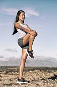 Leg stretching exercise fitness runner woman doing running warm-up, hamstring muscles stretch standing wtih single knee to chest stretch. Female athlete preparing legs for cardio workout. poster