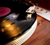 Close up of a vinyl record LP spinning on a turntable with arm and needle - vintage retro nostalgia poster
