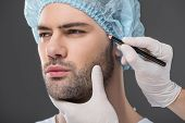 doctor drawing lines for facelifting on man, isolated on grey poster
