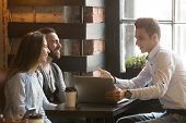 Insurance broker or salesman making offer to young millennial couple using laptop in cafe, realtor consulting customers about mortgage sitting at coffeehouse table pointing on computer screen poster