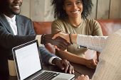 Happy young african american couple making deal handshaking caucasian insurance broker in cafe, black satisfied customer and realtor or sales person shaking hands at meeting in office with laptop poster